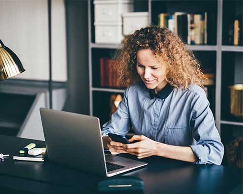 photo of woman using a laptop and cellphone