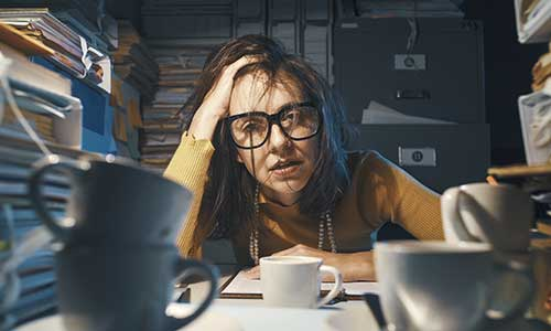 photo of a woman stressing out at a desk with a lot of books and coffee cups