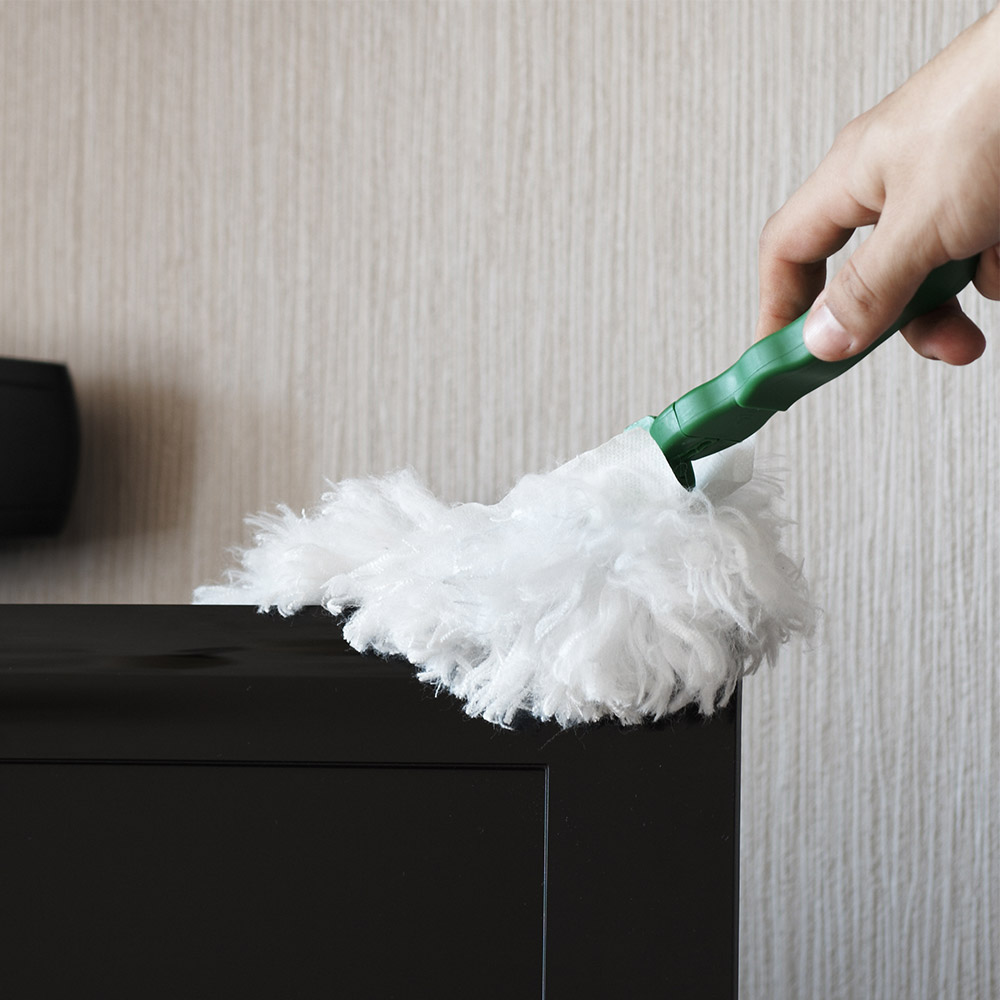 photo of a person dusting off a dresser