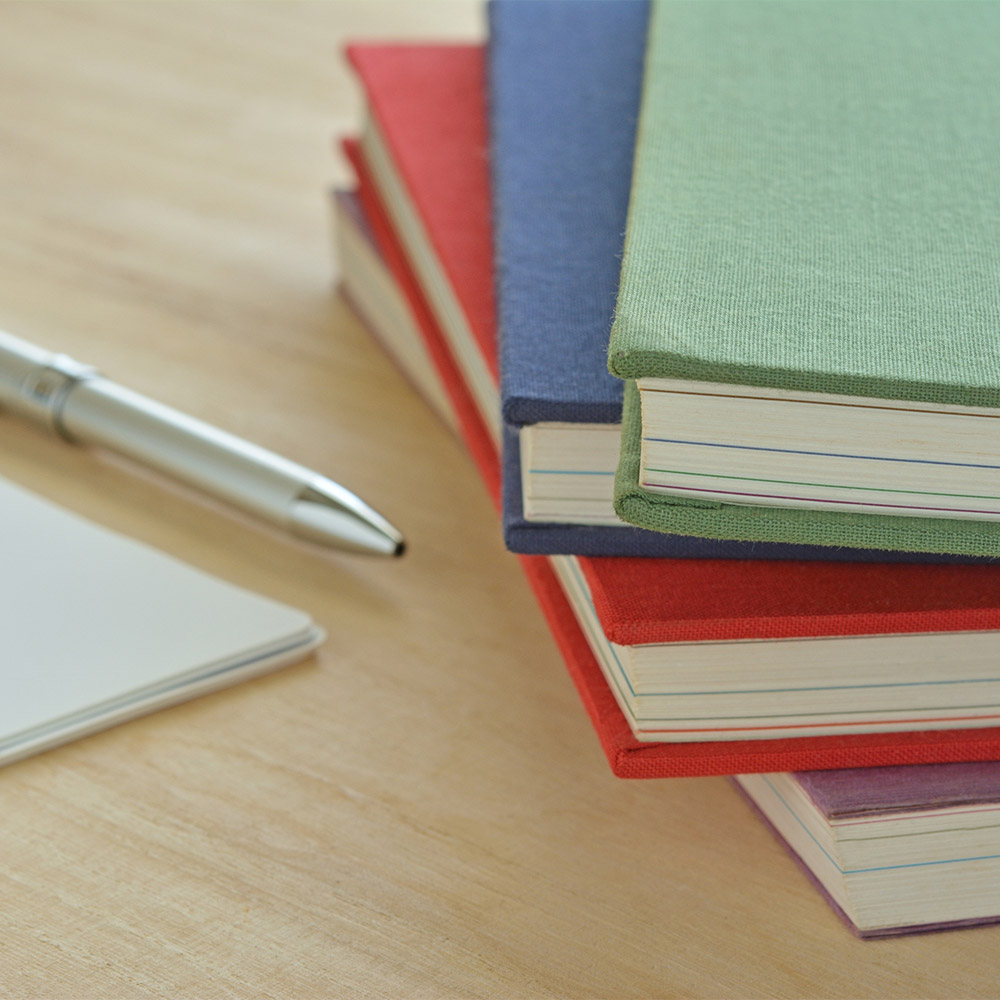 photo of a pen and notepad, and a stack of books on a table